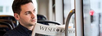 Mann mit Zeitung in einer Straßenbahn