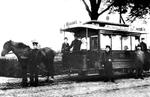 Pferd vor historischer Straßenbahn mit Fahrgästen